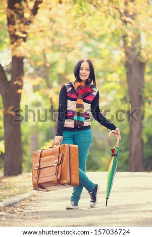 Brunette girl holding suitcase and umbrella at autumn alley in the park - stock photo