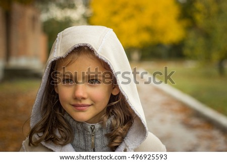 brunette girl in a light coat with a hood in yellow autumn leaves