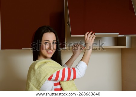 Brunette girl in home clothes opens the door cupboard. She stands dressed in blue overalls and a white T-shirt and on the shoulder of her green towel. She looks at the camera and smiling cheerfully. - stock photo