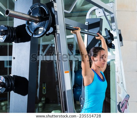 brunette girl in multipower barbell shoulder press Smith machine at gym - stock photo