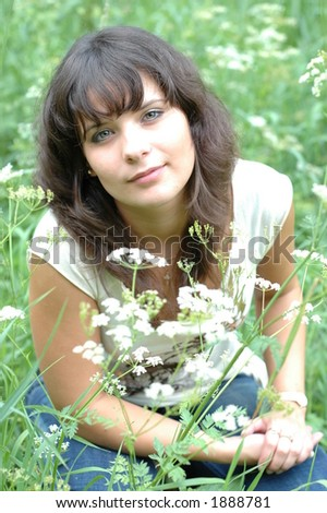brunette girl in summer time sitting in the grass