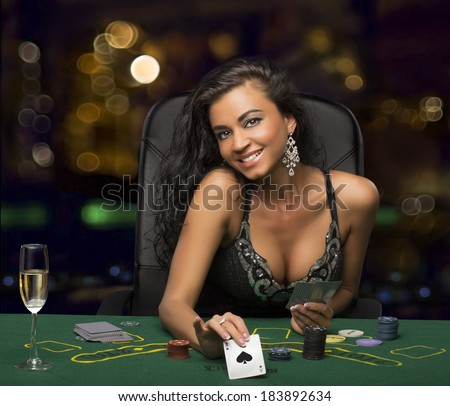 brunette girl in the casino playing poker, shows a playing card - stock photo