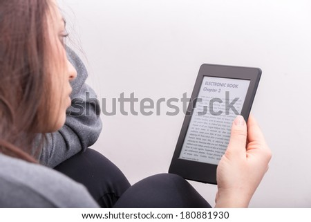 "Brunette GIrl is focused reading an electronic book with her Ebook Reader. The text on the ebook reader is an ""lorem ipsum"""