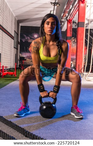 brunette girl kettlebell swing weightlifting workout exercise at gym - stock photo