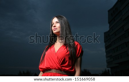 Brunette girl long hairs  in red dress against dramatic sky. Side view. Looking Up and Hands Crossed. Outdoor fashion shot - stock photo