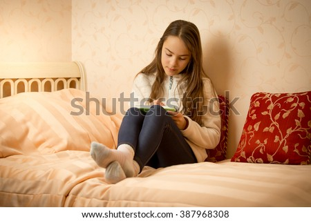 Brunette girl lying on bed with her private diary - stock photo
