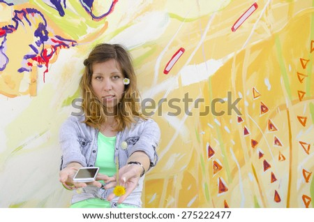 Brunette girl posing against a colorful backdrop holding daisies