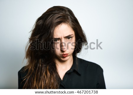brunette girl puffed out his cheeks, dressed in black, isolated on white background