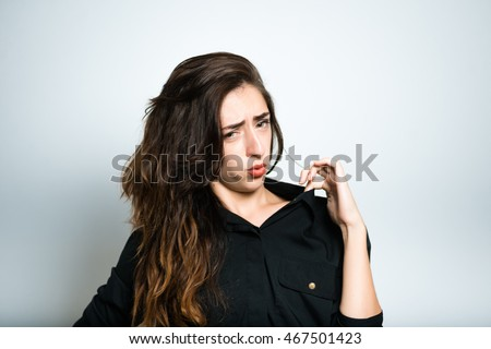 brunette girl pulls the collar, dressed in black, isolated on white background