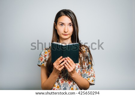 brunette girl reads and thinks over the notepad isolated on a gray background - stock photo