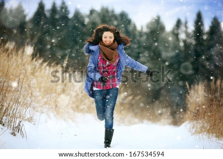 brunette girl running in a snowy forest - stock photo