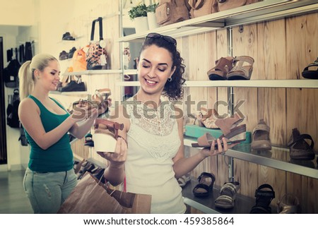 brunette girl showing a chosen pair of shoes while her friend still choosing - stock photo