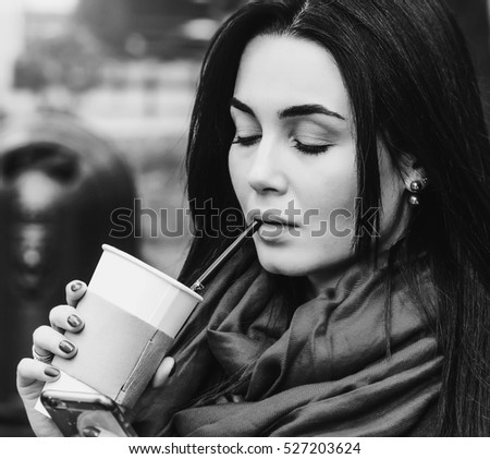 Brunette girl sitting in the park with coffee and phone