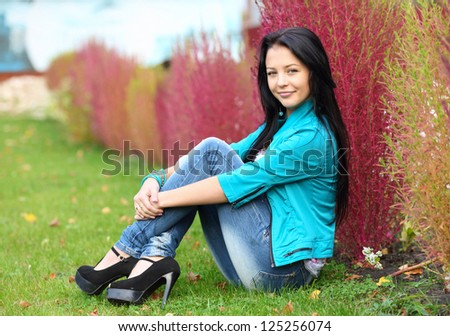 brunette girl sitting on grass - stock photo