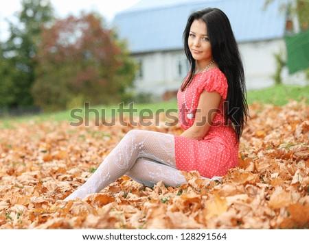 brunette girl sitting on the autumn leaves - stock photo