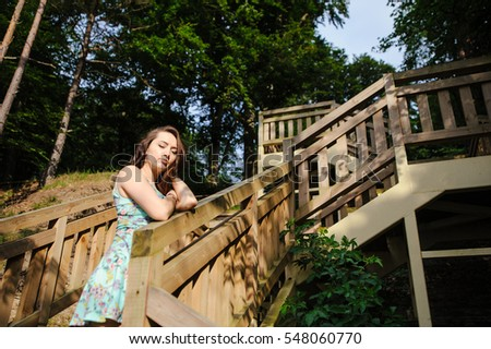 Brunette girl sitting on the wooden stairs in park and smiling