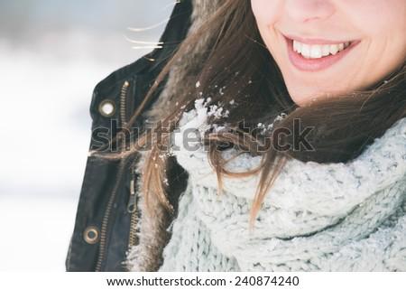 brunette girl smiling, snow on her hair - stock photo
