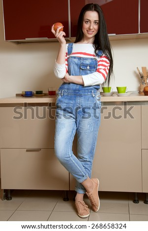 Brunette girl stands leaning on kitchen cupboard and holds an apple in his hand. She is dressed in blue overalls and a white shirt. On the background there is a kitchen in beige and maroon colors. - stock photo