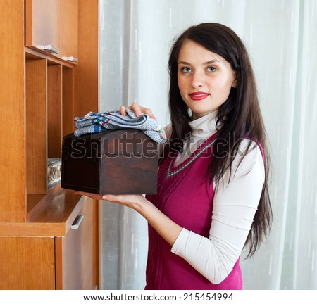 brunette  girl wiping the dust from wooden furniture