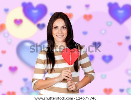 Brunette girl with a big lollipop and a background of colorful hearts - stock photo