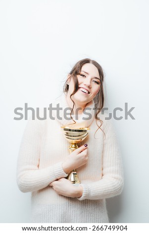 brunette girl with a cup winner in hands on a white background - stock photo