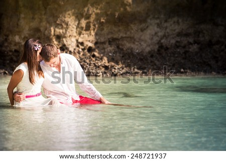 brunette girl with handsome man sitting in sea water in island bay with green mountain background