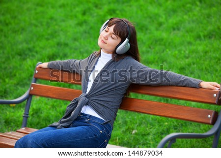 Brunette girl with headphones sitting at the bench in the park. - stock photo