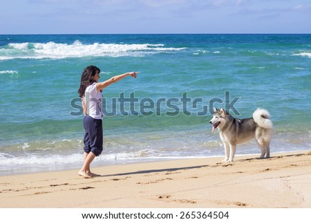Brunette girl with her Eskimo dog on sea beach at summer