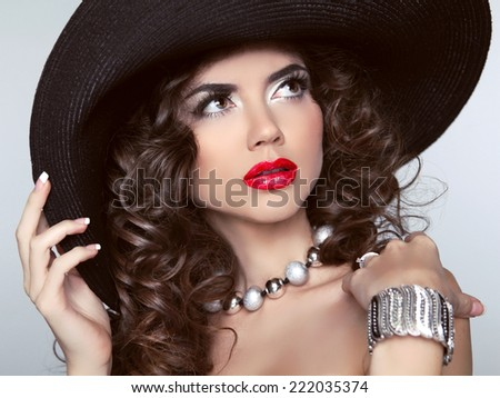 Brunette girl with red lips, makeup, wavy hair, fashion jewelry. Beautiful woman model in black hat.