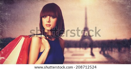 Brunette girl with shopping bags on Parisian background. - stock photo