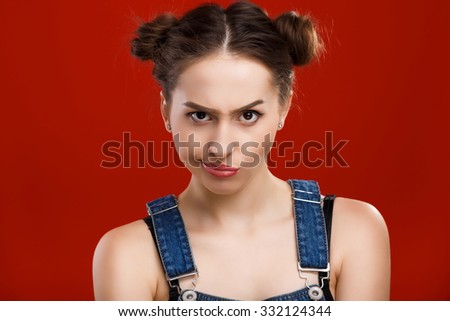 Brunette girl, with top knot hairdo, wearing on denim jumpsuit, posing with angry face expression, on the red background, in studio, waist up - stock photo