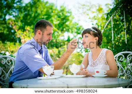 Brunette groom and bride sit at white table in cosy street cafe. bride and groom at  table of summer cafe. bride and groom feed each other