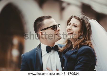 Brunette groom in sunglasses looks with proudly at a pretty bride - stock photo