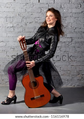 Brunette guitar player woman on the gray background
