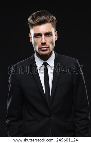 brunette handsome man in a suit on a dark background - stock photo
