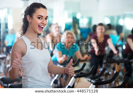 Brunette happy american girl and other females working out in sport club