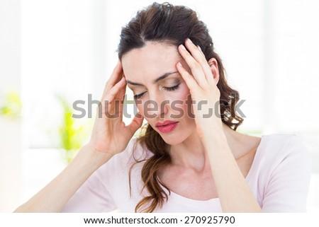 Brunette having headache on white background - stock photo