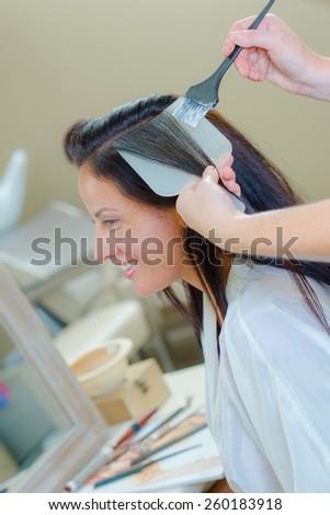 Brunette having her hair coloured - stock photo