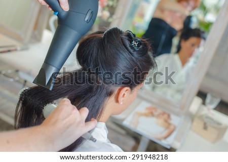 Brunette having her hair styled - stock photo