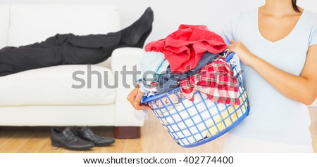 Brunette holding a basket full of laundry against low section of businessman resting on sofa in living room