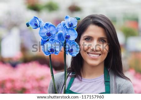 Brunette holding a blue flower in the garden centre - stock photo