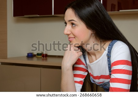 Brunette housewife wearing in blue denim overalls enthusiastically listens to someone. Girl looking slightly to the side and rests his hand on the table. She is standing in the kitchen and smiling - stock photo