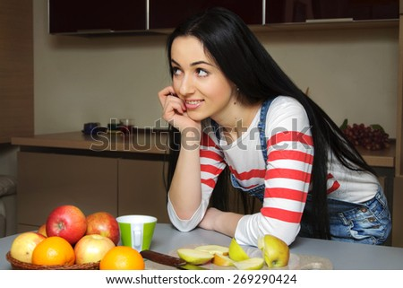 Brunette housewife wearing in blue denim overalls enthusiastically listens to someone. Girl looking slightly to the side and rests his hand on the table.  - stock photo