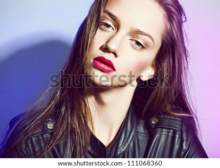 brunette in a black leather jacket and red lips - stock photo