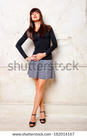 brunette in a dress posing against a wall