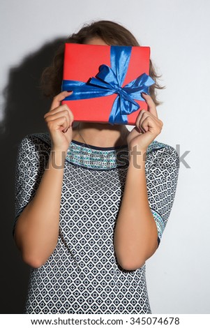 Brunette in a light dress covering her face with red gift on white background.