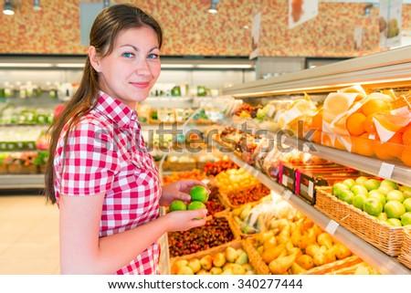 brunette in a supermarket chooses the lemons - stock photo