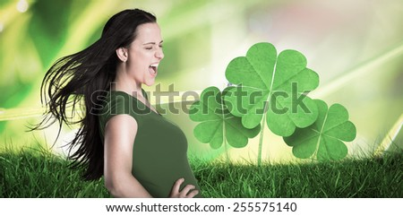 Brunette in green tshirt against dew on the grass close up - stock photo