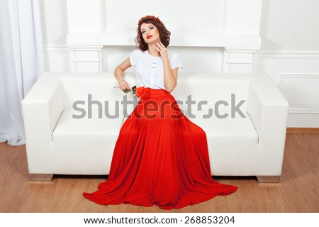 Brunette in red dress sitting on a white sofa and stroking his neck hand, she flirts. - stock photo