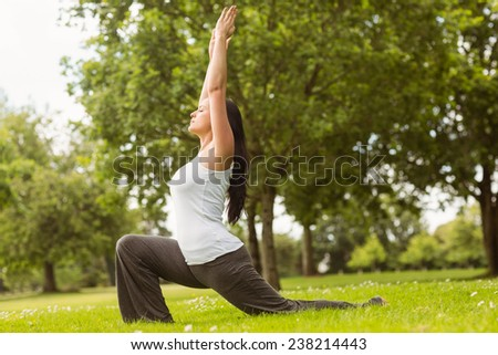 Brunette in warrior pose on grass in the park